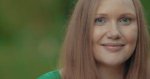 Woman Breaking into Broad Smile. Closeup shot of an adult woman breaking into broad smile stock footage