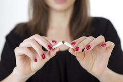 Woman breaking a cigarette. Young woman breaks a cigarette stock photography
