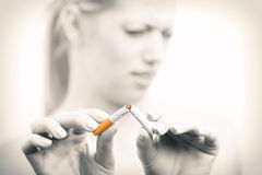 Woman breaking cigarette Stock Images