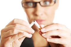 Woman breaking cigarette to stop smoking royalty free stock image