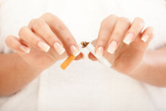 Woman breaking a cigarette royalty free stock photos