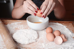 Woman breaking an egg into bowl. Royalty Free Stock Image