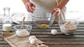 Woman breaking eggs into a bowl stock footage