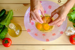 Woman breaking eggs into a bowl. On wooden table Stock Photos