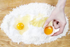Woman breaking eggs into four to make bread dough. Festive dessert Royalty Free Stock Images