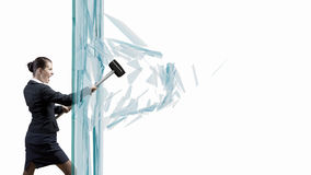 Woman breaking glass. Young determined businesswoman breaking glass with hammer stock images