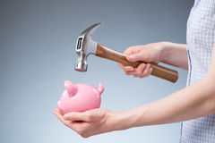 Woman Breaking Open a Piggy Bank Royalty Free Stock Photo