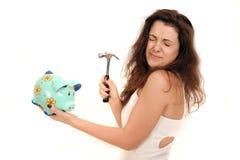 Woman breaking a piggy bank Stock Photo