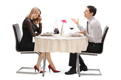 Woman breaking up with her boyfriend. Young women breaking up with her boyfriend seated at a restaurant table isolated on white background stock photography