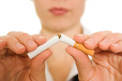 Woman breaks down the cigarette. Woman breaks down the cigarette on a white background royalty free stock photography