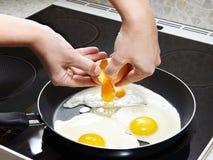Woman breaks an egg in fried eggs Stock Photo