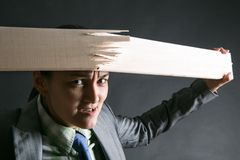Woman breaks wooden strip with hands Royalty Free Stock Image