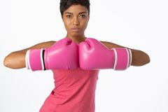 Woman for breast cancer awareness in boxing gloves. Standing woman for breast cancer awareness in boxing gloves on white background royalty free stock images