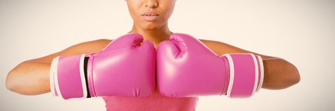 Woman for breast cancer awareness in boxing gloves. Standing woman for breast cancer awareness in boxing gloves on white background stock images