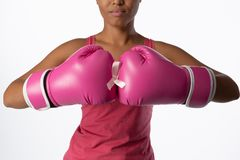 Woman for breast cancer awareness with ribbon in boxing gloves. Standing woman for breast cancer awareness with ribbon and boxing gloves on white background stock photos