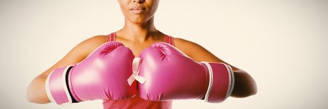 Woman for breast cancer awareness with ribbon in boxing gloves royalty free stock photo