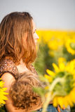 Woman breastfeeding baby. Young women breastfeeding her baby in spring sunflower field Royalty Free Stock Images