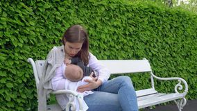 A Woman Breastfeeding her Child in the Park. A women breastfeeding her child in the park sitting on a bench. Medium shot Royalty Free Stock Image