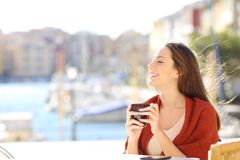 Woman breathing fresh air in a coffee shop on vacation. Side view portrait of a happy woman breathing fresh air in a coffee shop on vacation on the beach Stock Photos