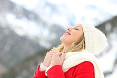 Woman breathing fresh air in the mountain in winter. Side view portrait of a woman breathing fresh air in winter with a snowy mountain in the background stock photography