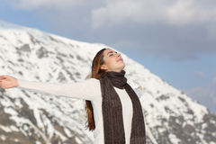 Woman breathing fresh air raising arms in winter royalty free stock photography