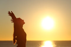 Woman breathing fresh air at sunset. On the beach and raising arms royalty free stock photos