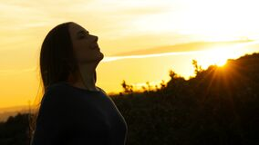 Woman is breathing fresh air at sunset stock video footage