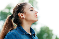 Woman breathing fresh air. Young attractive woman breathing fresh air outdoors showing his face to the wind Stock Images