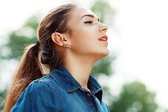 Woman breathing fresh air. Young attractive woman breathing fresh air outdoors showing his face to the wind Royalty Free Stock Photos