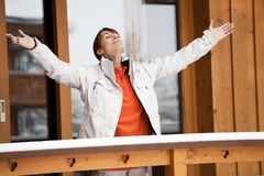 Woman breathing on her balcony in winter. Woman breathing on her balcony arms in the air in winter royalty free stock images