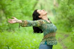 Woman breathing in nature. Beautiful woman taking a breath in verdant forest Royalty Free Stock Photography