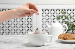 Woman brewing tea with bag in cup on table