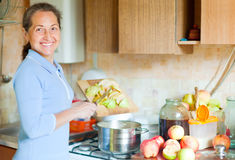 Woman brews apple jam. In the kitchen Royalty Free Stock Photography