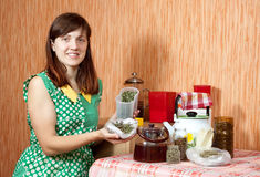 Woman brews herbs. In a teapot at home kitchen Stock Photos