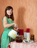 Woman brews herbs in teapot Royalty Free Stock Image