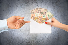 Woman bribing a man with an envelope full of money suggesting a corrupt system Royalty Free Stock Photography