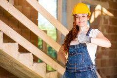 Woman Bricklayer Thumbs Up. Smiling Woman Bricklayer with Overalls and Helmet Thumbs Up Royalty Free Stock Photography