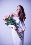 Woman in bridal dress with bouquet from roses Stock Photo