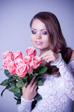 woman in bridal dress with bouquet from roses Royalty Free Stock Images