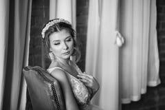 Woman in bridal dress sitting on armchair. Looking down. Indoor, interior, studio. Woman in pink bridal dress sitting on brown armchair. Looking down. Indoor Stock Photos