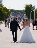 Woman in bridal gown and man in tuxedo walking on sidewalk in this tourist town after having gotten married stock photo
