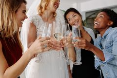 Woman in bridal gown toasting champagne glasses with friends royalty free stock image
