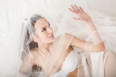 Woman in bridal lingerie covering her face using veil Royalty Free Stock Photo