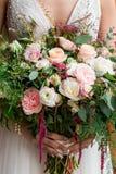 Bride holding pink rose wedding bouquet stock photo