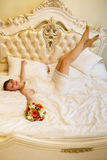 Woman - the bride with flowers in clothes on a bed Royalty Free Stock Image