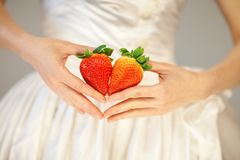 Woman bride hands holding some strawberries in her hands. Sensual studio shot can be used as background royalty free stock image