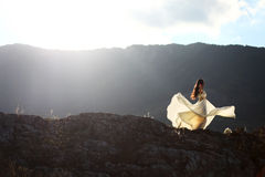 Woman in brides dress dancing. Beautiful bride dances on a mountain cliff in the middle of nature Stock Photo