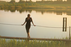 Woman on bridge. Sunset. Lake on background stock images