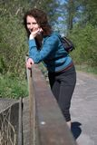 Woman on a bridge. Young woman in sport clothes standing on a bridge in a forest having a break during a trip Royalty Free Stock Photography