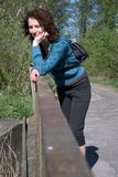 Woman on a bridge. Young woman in sport clothes standing on a bridge in a forest having a break during a trip Stock Image